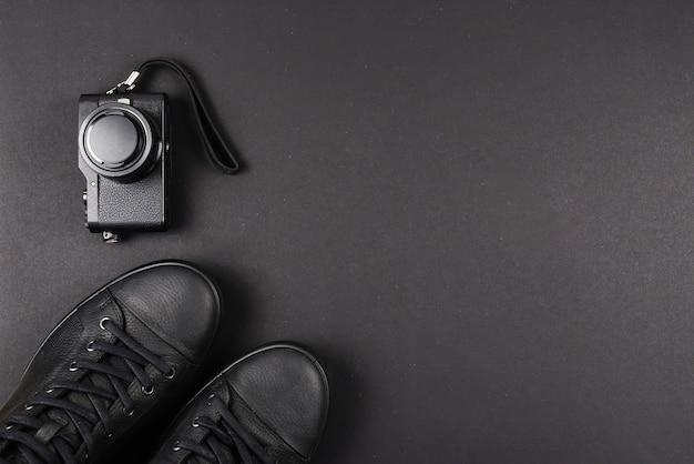 Мужские черные кожаные туфли и черный фотоаппарат на черной стене. скопируйте пространство.