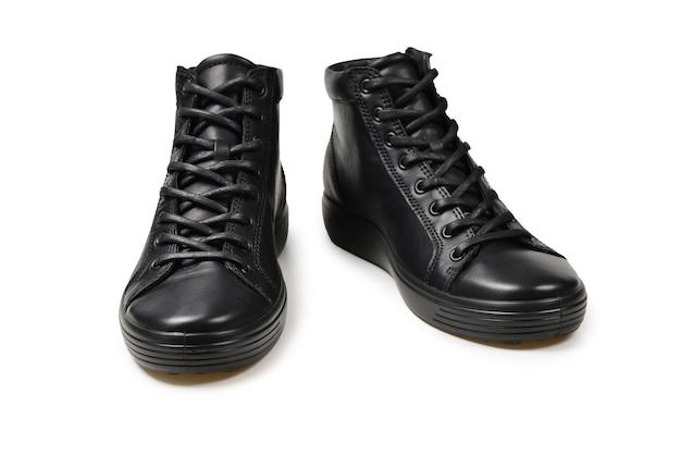 Мужские черные кожаные туфли и черная камера на изолированной на белой стене. скопируйте пространство.
