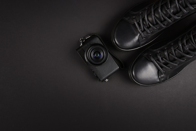 Men's black leather shoes and a black camera on a black background. copy space.