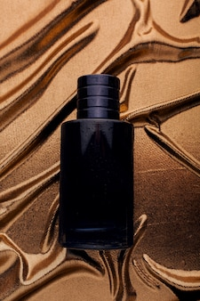 Men's black perfume on gold fabric