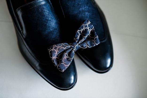 Мужские черные туфли и галстук. украшение мужчины на праздник.