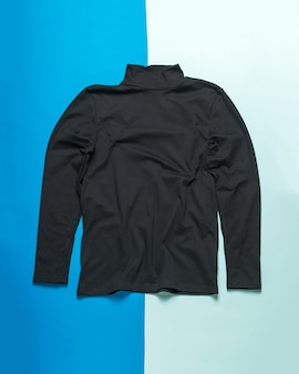Men's black sweater with long sleeves on a two-tone surface. classic men's stylish clothing.