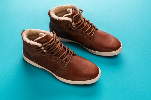 Men's brown winter shoes isolated on blue