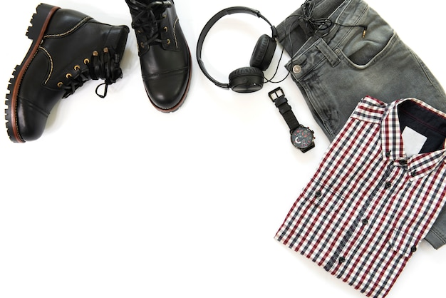 Men's casual outfits for man clothing with black ankle boot , watch, earphone, gray jeans and shirt isolated on white background, top view , copy space