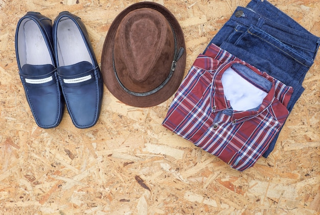 Men's casual outfits with leather accessories on wooden background, fashion concept.