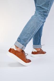 男性のカジュアルシューズは茶色で天然皮革を使用し、男性は茶色のレースの靴を履いています。高品質の写真