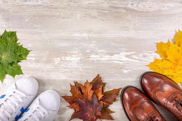 단풍 나무 잎이있는 나무 바닥에 남성용 클래식 한 갈색 가죽 신발과 운동화. 남자 브라운 신발.