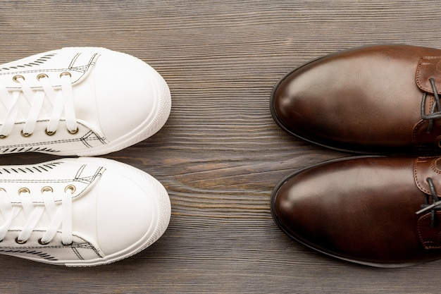 Men's classic brown shoes and white sneakers on a wooden