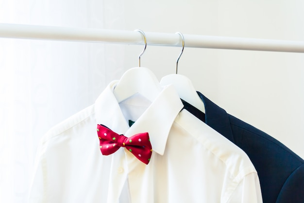 Men's classic white shirt with a red bow tie and a suit on a hanger