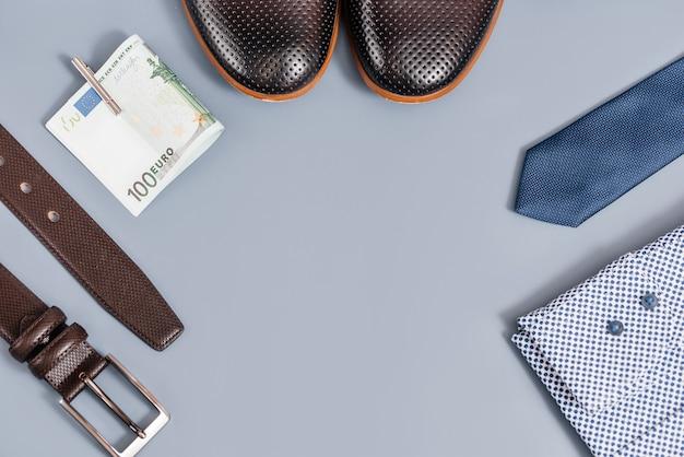 Мужская одежда и аксессуары. галстук и обувь, рубашка, пояс деньги. на синем фоне скопируйте пробел. вид сверху.