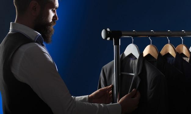 紳士服、ブティックでの買い物。仕立て、仕立て。スタイリッシュなメンズスーツ。メンズスーツ、彼のワークショップで仕立てます。古典的な衣装のスーツでハンサムなひげを生やしたファッション男。男性のスーツが一列にぶら下がっています。