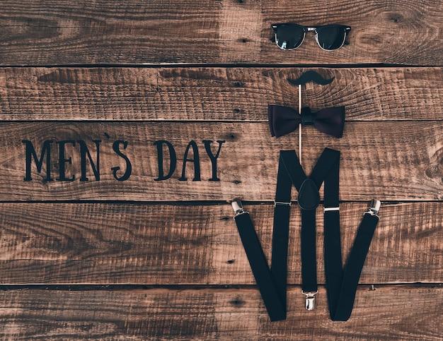 Мужской день. снимок с высоким углом подтяжек, реквизита, галстука-бабочки и очков, лежащих на деревянном столе