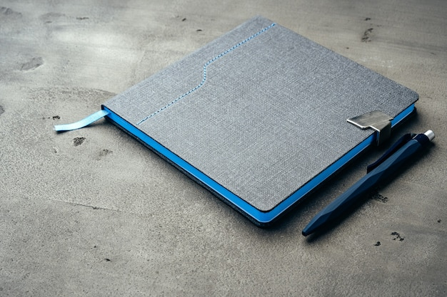 Мужской дневник и ручка на темно-сером фоне крупным планом