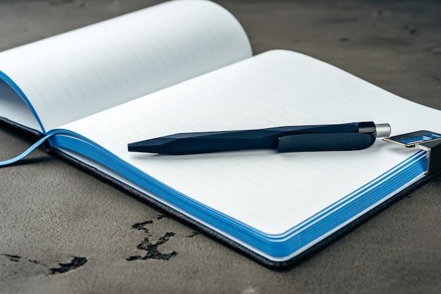濃い灰色の背景に男性の日記とペンをクローズアップ