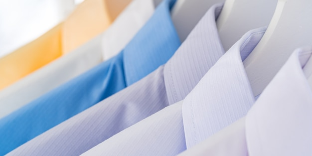Men's dress shirts, clothes on hangers on white background