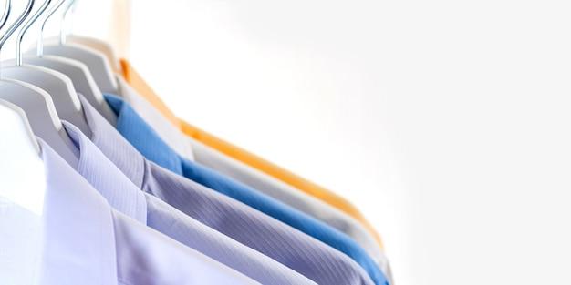 Мужские классические рубашки, одежда на вешалках на белом фоне