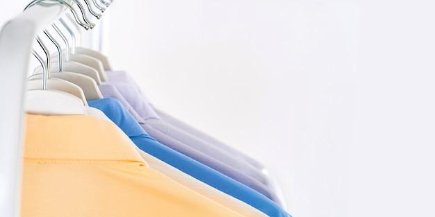 Рубашки мужские, одежда на вешалках на белой стене