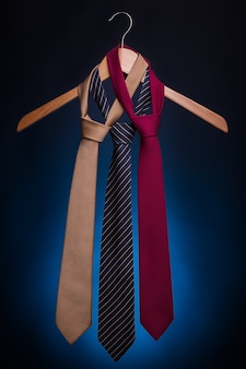 Men's fashionable ties on a hanger. on a blue background.