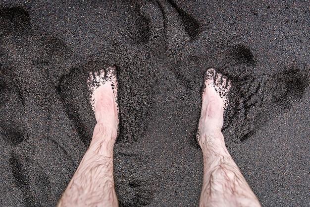 男性の足は火山の黒い砂の上にあります。