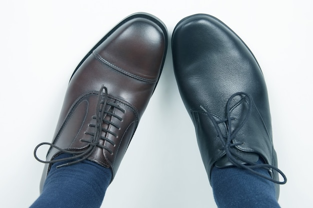 異なる色の古典的な靴の男性の足
