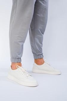 Мужские ножки в белых повседневных кроссовках из натуральной кожи на шнуровке. фото высокого качества