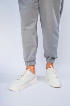Мужские ножки в белых повседневных кроссовках из натуральной кожи на шнуровке.