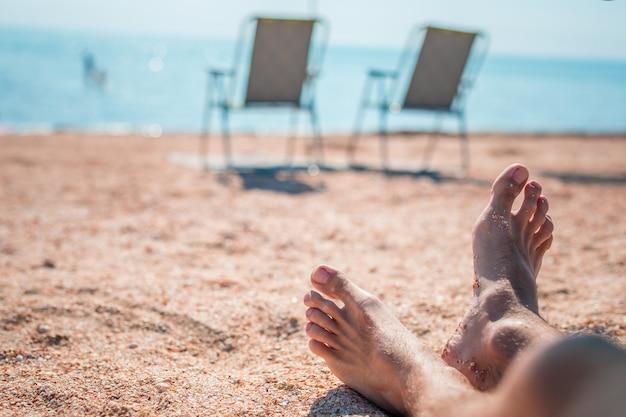 Men's feet on lounge in bungalow sea view