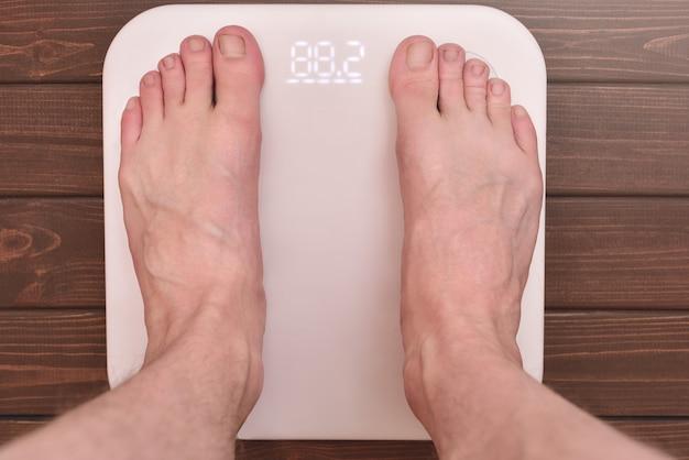 Мужские ноги на современных электронных весах. спортивная концепция