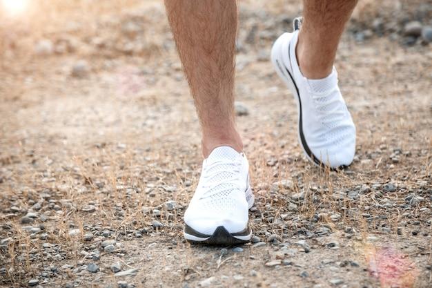 Men's feet in white sneakers running over rough terrain. cross country running with focus on runner's legs.