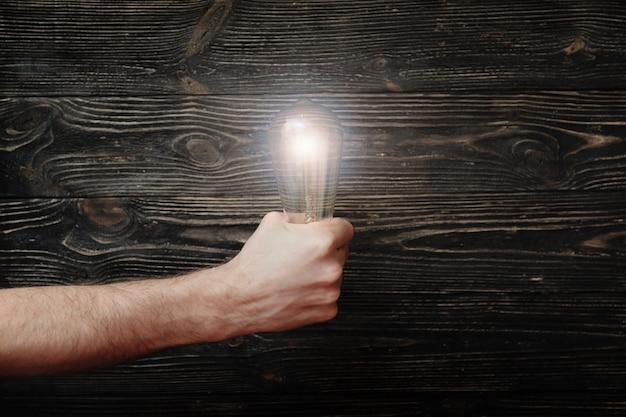 어두운 나무 배경에 빛나는 전구를 가진 남자의 주먹. 대담한 아이디어의 개념