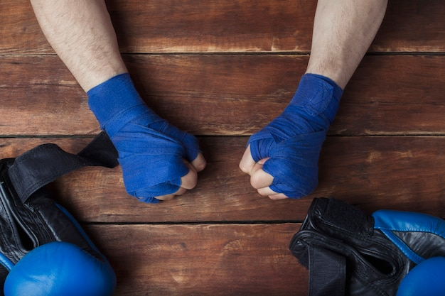 Men's fists in boxing taping on a wooden background with boxing gloves. concept of training for boxing training or fighting.