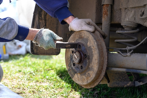 Men's gloved hands repair of car drum brake himself. disassembles a jammed disk with a hammer. repair of broken car drum brake disassembled outdoor