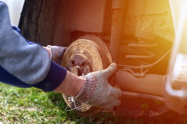 Men's gloved hands repair of car drum brake himself. repair of broken car drum brake disassembled outdoor. flare