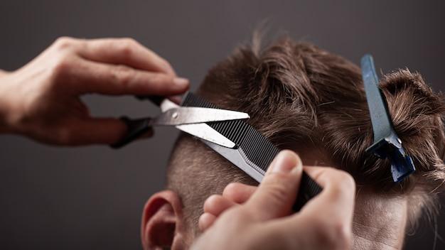 Мужская стрижка. мастер режет человека с ножницами крупным планом.