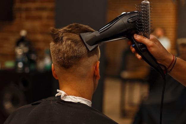 男性の髪型。ヘアドライヤーでスタイリング。理髪店