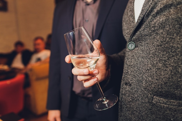 Men's hand holding wine glass at festive event.