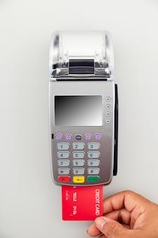 男性の手がターミナルに赤いクレジットカードを持っています