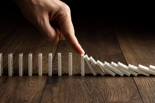 Men's hand stopped domino effect, on a brown wood