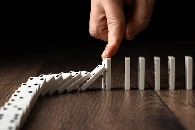 Men's hand stopped domino effect