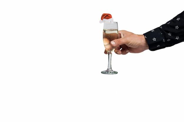 남자의 손은 산타클로스 모자로 장식된 샴페인 한 잔을 받습니다. 크리스마스, 크리스마스, 신년 파티. 남자는 흰색으로 격리된 와인 잔을 들고 있습니다. 술을 한 잔 든 인간의 손, 축배