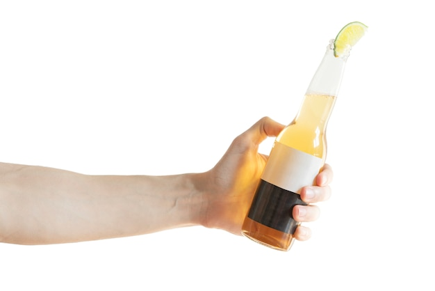 Men's hand tilts or cheers a glass bottle of light beer with a slice of lime in bottle neck isolated on white