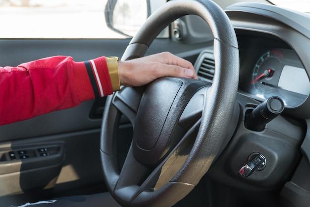 Мужская рука с часами на руле современного автомобиля