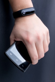 Men's hand with a fitness tracker and smartphone