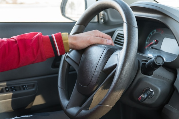 Men's hand with a watch on the steering wheel of a modern car