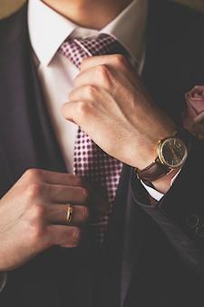 男性の手はネクタイのクローズアップを調整します。ビジネスマン、起業家、高価な時計、単にファッションの古典的なスーツである成功した若い男。 。