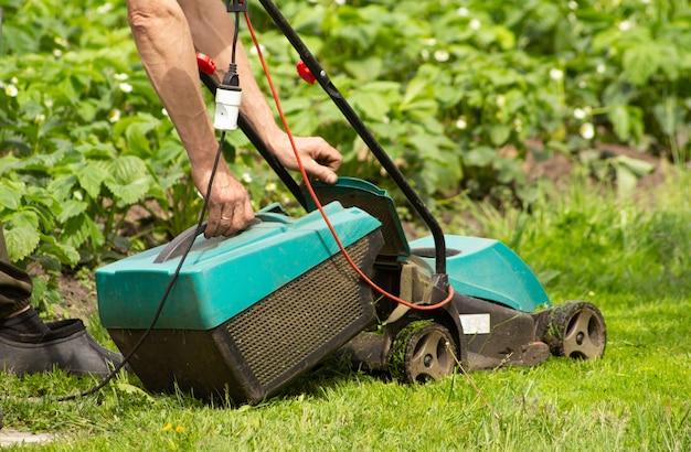 남자의 손은 전기 잔디 깎는 잔디 수신기에서 가져옵니다. 그는 정원에서 풀을 깎았습니다.