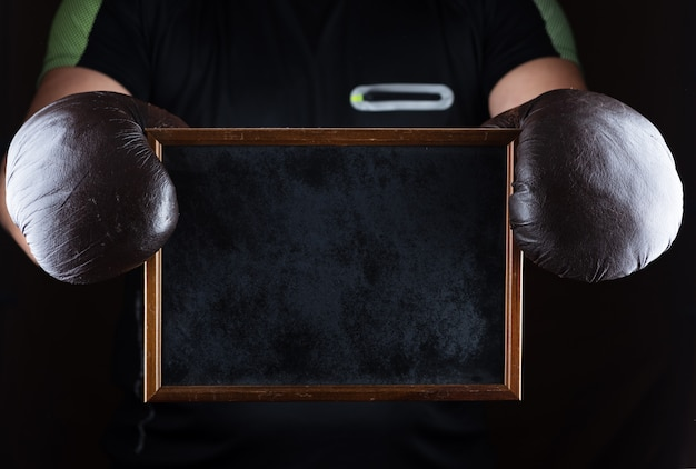 Men's hands in boxing gloves hold an empty black frame