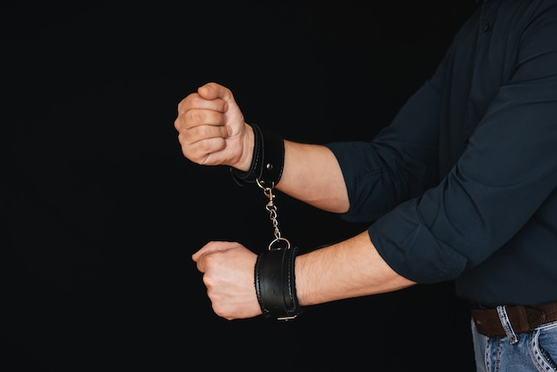 Men's hands chained in leather handcuffs on black