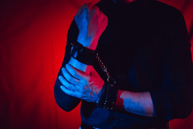 Men's hands chained in leather handcuffs