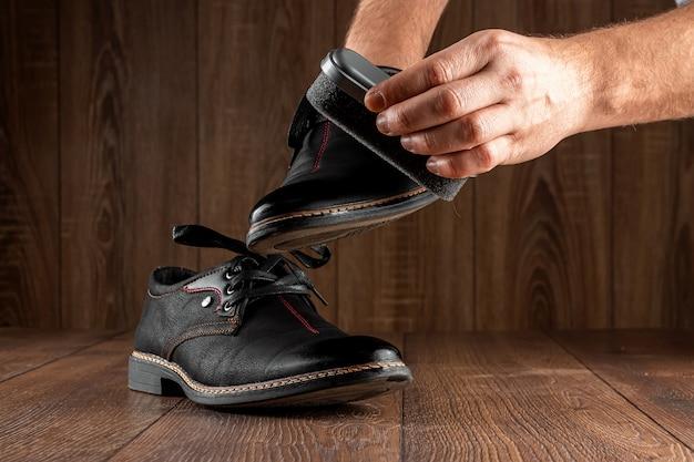 Мужские руки чистят черные туфли на деревянной стене. концепция обуви, уход за одеждой, услуги.